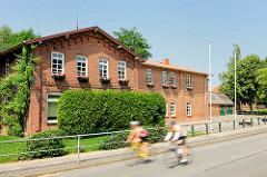 Ehemaliges Schuldgebäude in Wakendorf II; Kreis Stormarn - Radfahrer auf der Strasse.