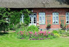 Bauerngarten, Wiese mit Blumen; Reetdachhaus in Wakendorf II.