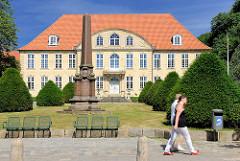Gebäude Amtsgericht Schleswig - Obelisk auf dem Rasen - Fussgänger.