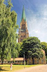 Kirchturm des St. Petri Doms in Schleswig zwischen Bäumen - eine Touristin fotografiert das Gebäude.