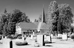 Schwarz weiss Aufnahme - Friedhof und Gemeindehaus Tangstedt, Kreis Stormarn - Grabsteine und hohe Bäume, Spitze vom Kirchturm.