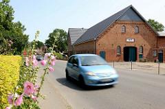 Stockrosen am Strassenrand - Strassenverkehr und landwirtschaftliches Ziegelgebäude in Wakendorf II - Kreis Stormarn.
