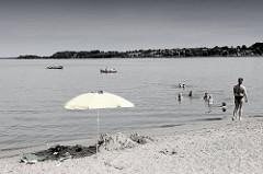 Badestrand an der Schlei in Schleswig - Sandstrand beim Neubaugebiet Auf der Freiheit. Badende Familien im Wasser - Sonnenschirm im Sand; Boote auf der Schlei.