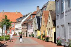 Wohnhäuser - Einfamilienhäuser an der Marktstrasse in Schleswig - Rosenstöcke mit blühenden Rosen an der Hauswand.