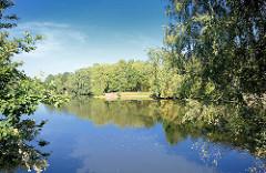 See am Stadtpark in Norderstedt - Bäume am Seeufer.
