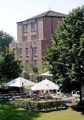 Gebäude Park Hotel in Norderstedt - Aussangastronomie mit weissen Sonnenschirmen in der Sonne.