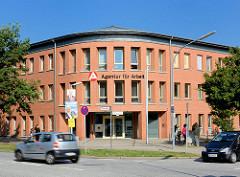 Gebäude AGENTUR FÜR ARBEIT in Norderstedt an der Rathausallee - Bürohaus mit roter Fassade - Architektur der 1980er Jahre.