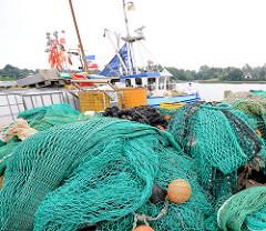Stapel grüne Netze am Kai vom Fischereihafen in Kappeln - im Hintergrund die Schlei und ein Fischereischiff.