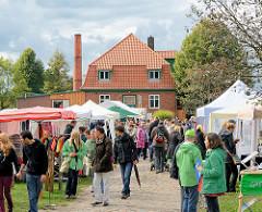 Bauernmarkt auf dem Biohof in Wulksfelde - BesucherInnen gehen zwischen den Ständen der Aussteller; im Hintergrund das Gebäude der Gutsküche.