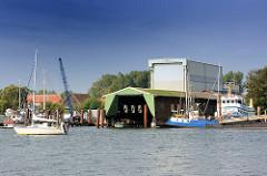 Blick über die Schlei zur Stadt Arnis. Werfthallen am Wasser der Schlei - ein Segelboot fährt unter Motor Richtung Schleswig.