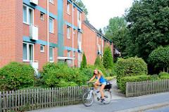 Mehrstöckige Neubauten in Glashütte, Norderstedt; Architekturbilder unterschiedlicher Architekturrichtungen. Büsche und Sträucher im Vorgarten - Staketenzaun aus Holz.
