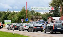 Kartoffelmarkt in Wulksfelde, Gemeinde Tangstedt - Autoschlange auf der Strasse; Banner mit der Aufschrift Kartoffelmarkt.