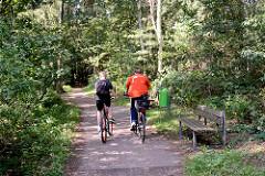 Waldweg mit Radfahrern im Ossenmoorpark in Glashütte, Norderstedt - Holzbank und Abfallkorb am Wegesrand.