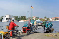 Autofähre / Personenfähre - Seilfähre über die Schlei bei Arnis, Schleswig Holstein. Fahrradfahrer mit Anhänger fahren auf die Seilfähre über die Schlei - im Hintergrund die Stadt Arnis.