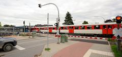 Die Schranken über die Quickborner Strasse in Friedrichsgabe / Norderstedt sind geschlossen, ein Zug der AKN fährt in den Bahnhof ein.