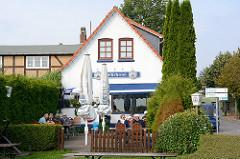 Fährhaus, Restaurant und Cafe an der Fähre über die Schlei bei Arnis. Gäste sitzen in der Sonne im Garten.