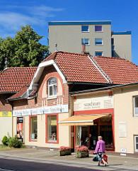 Historisches Wohnhaus - Einzelhandel, mehrstöckiger Wohnblock im Hintergrund - Motive aus der Stadt Norderstedt / Garstedt, Schleswig Holstein.