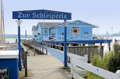 Holzhaus, blau gestrichen an der Schlei in Arnis - Zur Schleiperle, Restaurant und Cafe auf dem Wasser.
