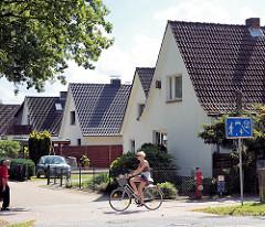 Einzelhäuser mit Spitzdach - Wohnhäuser in Glashütte, Norderstedt; Fussgänger und Radfahrerin - Strassenschild verkehrsberuhigte Strasse.