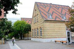 Restaurierte Architektur - Ziegelgebäude, Ziegeldach mit Dekor / Muster; ehem. Mittelschule / Schulgebäude.