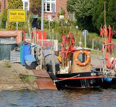 Ortschild Stadt Arnis - Fischereiboote mit roten Fahnen.