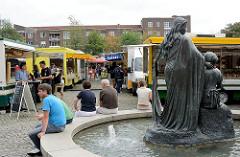 Wochenmarkt auf dem Platz vor dem Norderstedter Rathaus - rechts der Brunnen DIE REGENTRUDE; Bildhauer Hans-Werner Könecke; Szene aus der Novelle Theodor Storms - die Regentrude legt schützend den Arm um das Bauernmädchen Maren.