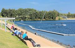 ZuschauerInnen an der Wasserskianlage im Stadtpark  Norderstedt.