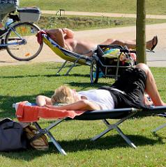 Norderstedter Stadtparkbesucher liegen auf Liegen in der Sonne.