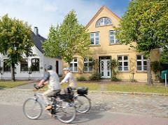 Lange Strasse in Arnis, der kleinsten Stadt Deutschland - historische Fischerhäuser; Fahrradfahrer auf ihren Rädern in Fahrt.