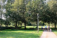 Grünanlage Moorbekpark in Norderstedt Nähe Rathausallee;  Fussweg, Spazierweg an der Moorbek - Spaziergänger.