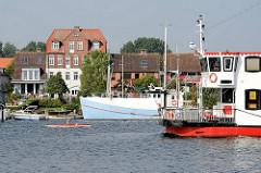 Schiffsverkehr auf der Schlei  - Fahrgastschiff und Kanu auf dem Wasser; am Ufer ein Fischereiboot - Häuser der Stadt Arnis.