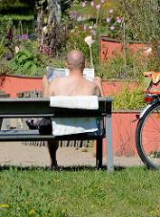 Besucher des Stadtparks in Norderstedt sitzt in der Sonne auf einer Bank und liest Zeitung.