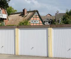 Reetdachkate - Wohnhaus mit Reet gedeckt, Fachwerkhaus - Norderstedt / Garstedt. Garagen mit Metalltor im Vordergrund.