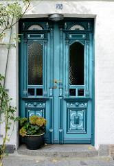 In Blautönen dekorierte Holztür - Eingang eines Wohnhauses in Arnis; Gründerzeit / Historismus.