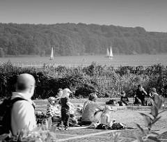 Wiese am Ufer des Ratzeburger Sees in Ratzeburg - Kinderspielplatz, einige Segelboote auf dem Wasser - Schwarz - Weiss Fotografie.