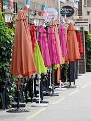 Zusammengeklappte bunte Sonnenschirme eines Restaurants an der Rathausallee in der Stadt Norderstedt - Schleswig Holstein.