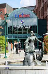 Eingang Rathaus, Tribüne in Norderstedt - Brunnen DIE REGENTRUDE; Bildhauer Hans-Werner Könecke; Szene aus der Novelle Theodor Storms - die Regentrude legt schützend den Arm um das Bauernmädchen Maren.