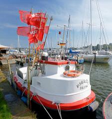 Fischereiboot im Hafen von Arnis, rote Positionsfahnen flattern im Wind - im Hintergrund ein Sportboothafen - Marina an der Schlei.