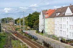 Wohnblocks / Wohnhäuser an der Güterbahnstrecke Wismar - im Hintergrund ein Stellwerkgebäude, beschrankter Bahnübergang.
