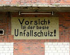 Handgemaltes Schild an der Fassade eines stillgelegten Silos im Hafen von Wismar - VORSICHT IST DER BESTE UNFALLSCHUTZ.