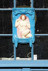 Holzschnitzerei am Fenster vom Eingang U-Bahnstation Schmalenbeck, Gemeinde Grosshansdorf - Vignette nackte Frau in blauem Rahmen.