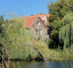 Blick vom Kurpark über den Mühlengraben in Mölln - zwischen Bäumen und Schilf ein Gebäude mit Holzfassade.