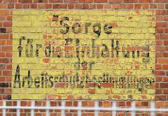 Handgemaltes Schild an der Fassade eines stillgelegten Silos im Hafen von Wismar - SORGE FÜR DIE EINHALTUNG DER ARBEITSSCHUTZBESTIMMUNGEN.