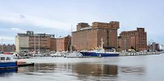Blick über das Hafenbecken des Hafens der Hansestadt Wismar - das Polizeiboot / Küstenstreifenboot HOBEN der Wasserschutzpolizei Mecklenburg-Vorpommern liegt am Kai; im Hintergrund verlassene Speichergebäude / Silos im Wismarer Hafen.