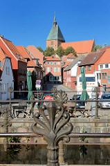 Dekorgeländer Eisen am Mühlengraben in der Stadt Mölln - im Hintergrund der Mühlenplatz und die Altstadt sowie die Möllner St. Nicolai-Kirche.