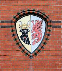 Wappen von Mecklenburg Vorpommern an der Ziegelfassade / Backsteinfassade des historischen Postgebäudes in Wismar. Schwarzer Stierkopf - roter Greif.