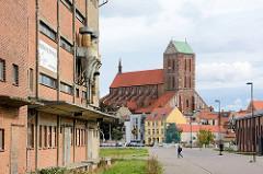 Stillgelegtes, verlassenes Silogebäude / Speichergebäude im Hafengebiet der Hansestadt Wismar - Industriearchitektur, Ziegelbau. Im Hintergrund die Wismarer St. Nikolai Kirche.