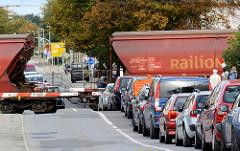 Güterverkehr im Hafengebiet der Hansestadt Wismar - die Schranken sind herunter gelassen - Autos warten / Stau; ein Güterzug überquert die Strasse.