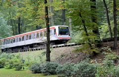 Bahnstrecke Walddörferbahn - endgültig eröffnet 1921; ein U-Bahnzug fährt auf einer Trasse zwischen Bäumen Richtung Station Großhansdorf.