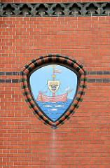 Wappen der Hansestadt Wismar an der Ziegelfassade / Backsteinfassade des historischen Postgebäudes. Schwimmende Kogge, schwarzer Stierkopf - Möwe, drei Fische.